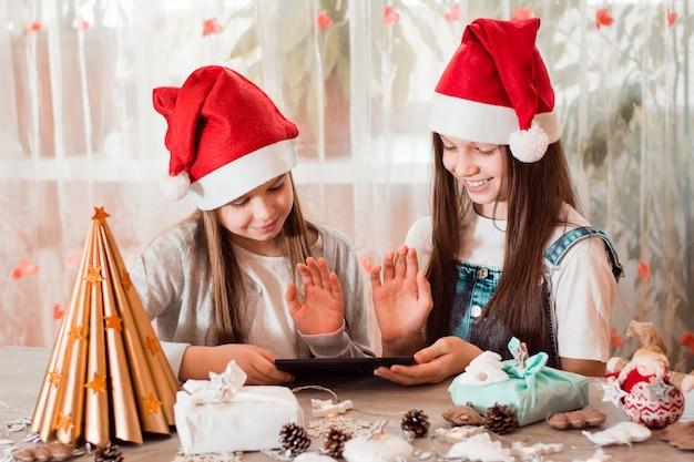 Gratulacje w kwarantannie. dziewczyny w ozdób choinkowych witają się i komunikują ze swoimi rodzinami za pośrednictwem tabletu.