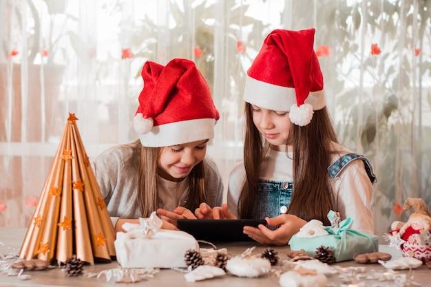 Gratulacje w kwarantannie. dziewczyny w świątecznych dekoracjach komunikują się ze swoimi rodzinami za pośrednictwem tabletu.