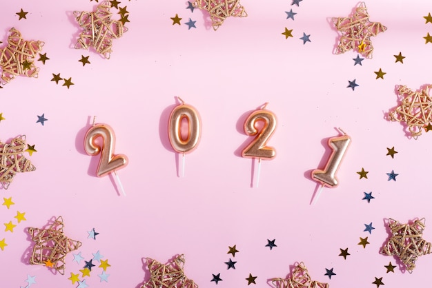 Gratulacyjna kartka noworoczna z figurami 2021, jasnym konfetti i dekoracją gwiazd na jasnoróżowym tle. leżał na płasko.