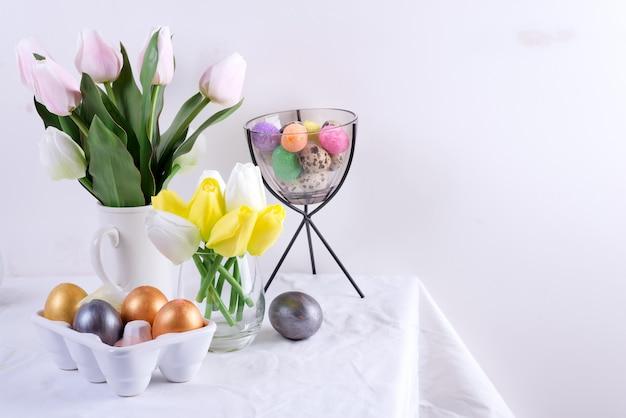 Gratulacyjna kartka wielkanocna serwowanego stołu z wiosennymi kwiatami i ręcznie malowanymi jajkami na jasnoszarej ścianie.