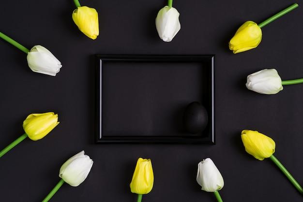 Gratulacyjna kartka wielkanocna ze świeżych kwiatów tulipanów i ramki z malowanym czarnym jajkiem na czarnym tle.