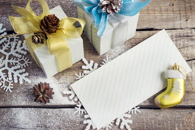 Gratulacyjny list prezenty świąteczne płatki śniegu świąteczne zabawki i guzy na drewnianym tle