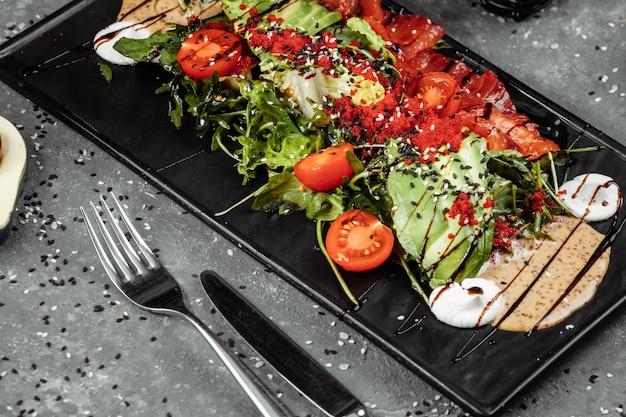 Gravlax z sałatką z łososia. sałatka z wędzonym łososiem, z mixem zieleni, pomidorkami koktajlowymi, awokado, czarnymi oliwkami, marchewką, kiełkami, ogórkiem i limonką. pyszne zdrowe odżywianie