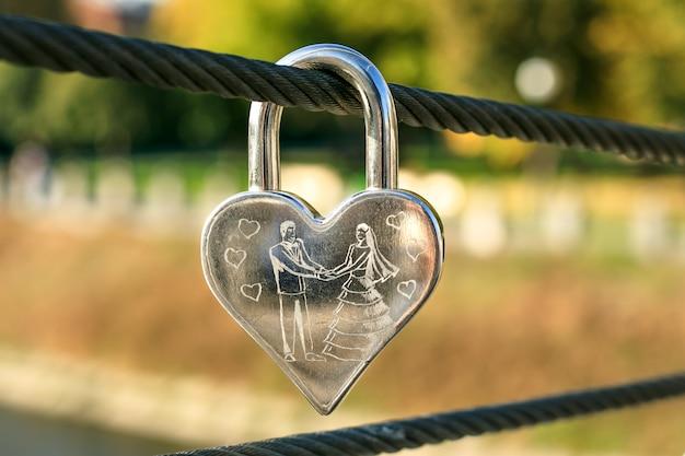 Grawerowana metalowa kłódka w kształcie serca.