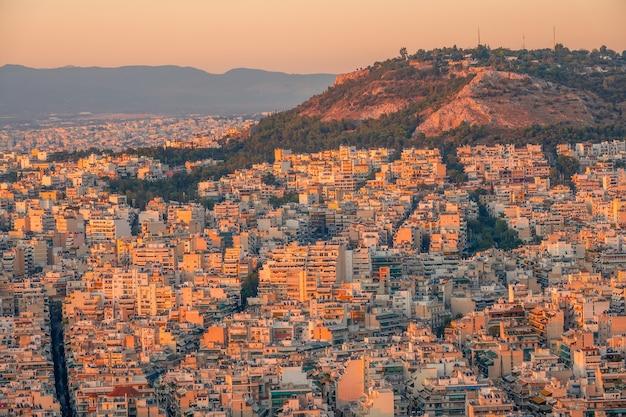 Grecja. cichy letni wieczór. widok na dachy aten o zachodzie słońca