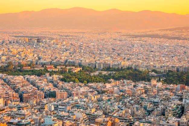 Grecja. ciepły letni wieczór nad dachami aten. budynki mieszkalne i biurowe oraz wąskie uliczki. zielone parki. widok z lotu ptaka