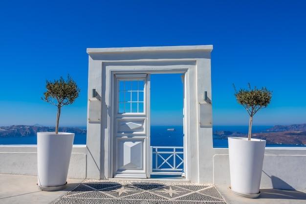 Grecja. letni słoneczny dzień na kalderze wyspy thira (santorini). wejście do kawiarni z widokiem na morze