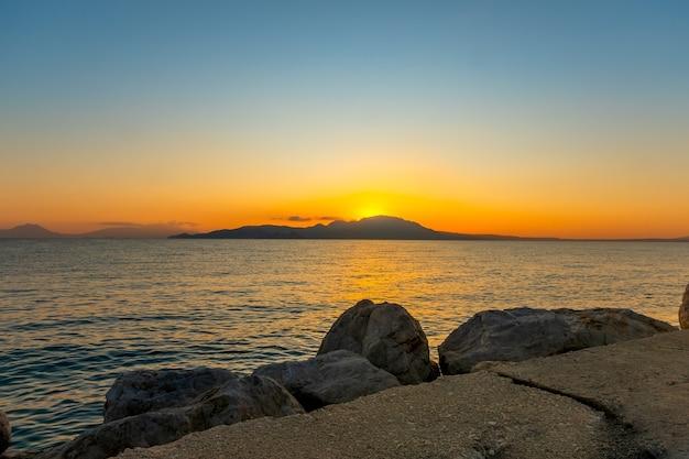Grecja. miasto kiato nad brzegiem zatoki korynckiej. ze względu na góry po drugiej stronie zatoki słońce wzejdzie za 3 minuty