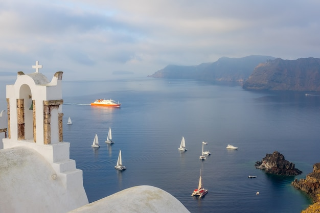 Grecja. pochmurny dzień na santorini. widok z greckiego kościoła z krzyżem w oia na zatokę z jachtami żaglowymi i statkiem wycieczkowym
