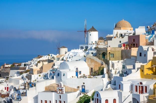 Grecja. santorini (thira). białe domy i wiatraki na zboczu góry w wiosce oia