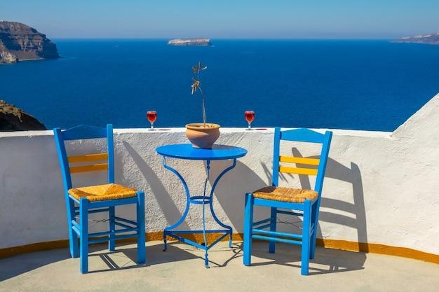 Grecja. santorini. wyspa thira. słoneczny krajobraz z kawiarni w oia. dwie lampki wina i dwa krzesła