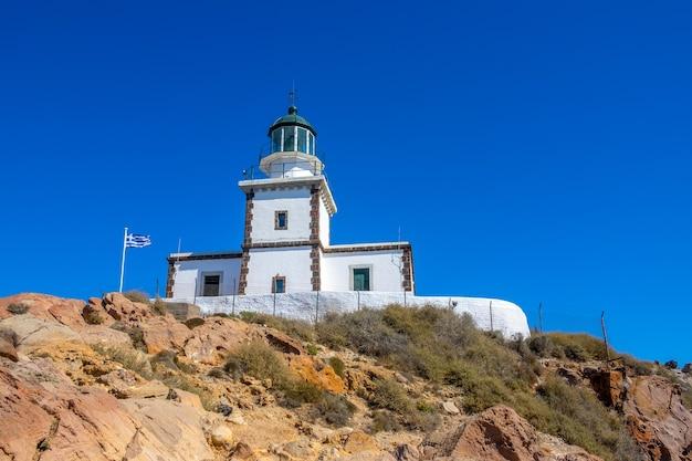 Grecja. skalista góra w bezchmurny dzień. budynek latarni na tle błękitnego nieba i flagi narodowej
