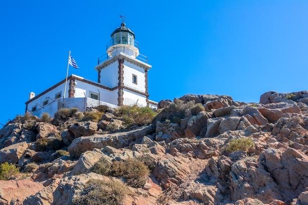 Grecja. skalista góra w słoneczny dzień. budynek latarni morskiej i flaga narodowa przeciw błękitne niebo