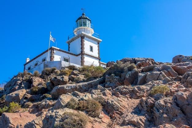 Grecja. skalista góra w słoneczny dzień. budynek latarni na tle błękitnego nieba i flagi narodowej