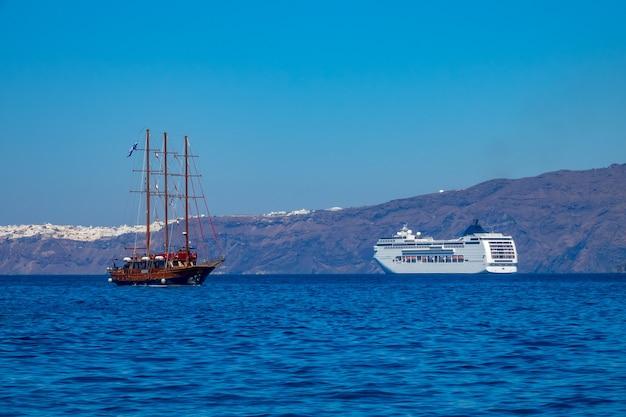 Grecja. słoneczny dzień u wybrzeży santorini. statek wycieczkowy wielopokładowy i stary statek trójmasztowy