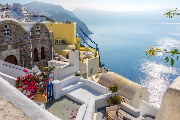 Grecja. słoneczny letni dzień na santorini. budynki i tarasy z kwiatami na kalderze z widokiem na morze