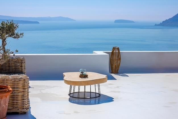 Grecja. słoneczny letni dzień na santorini. stół na kamiennym tarasie z widokiem na morze