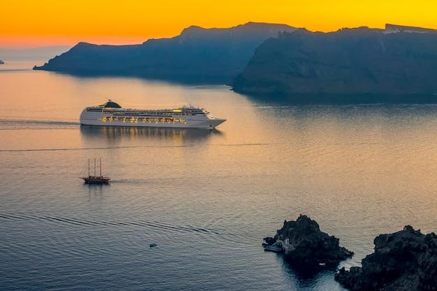 Grecja. widok na morze z oia (santorini, wyspa thita) o zachodzie słońca. duży statek wycieczkowy w lagunie i mały żaglowiec