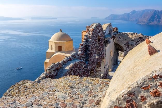 Grecja. wyspa santorini (thira) przy słonecznej pogodzie. kościół i stare ruiny na kalderze w oia. panoramiczny widok na morze
