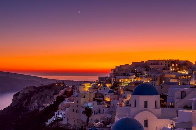 Grecja. wyspa thira. dachy oia podczas kolorowego zachodu słońca