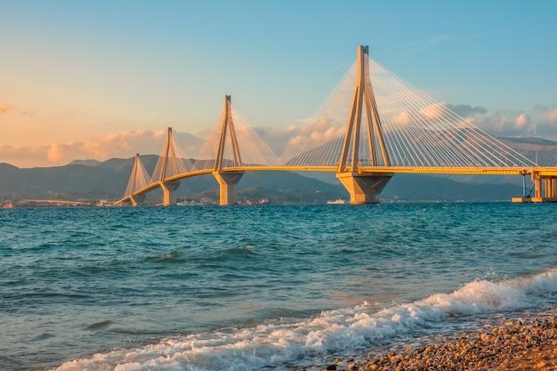 Grecja. zatoka koryncka i most rio antirio. oświetlenie zachodu słońca na kamienistej plaży