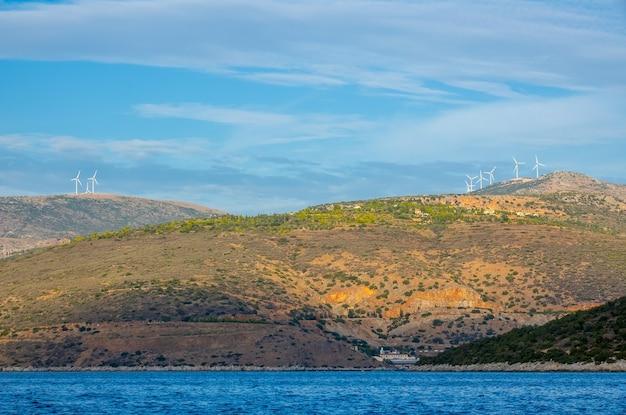 Grecja. zatoka koryncka. pagórkowate brzegi z farmami wiatrowymi na wzgórzach. widok z łodzi