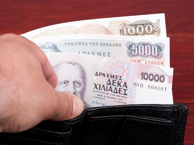 Grecka drachma pieniężna w czarnym portfelu