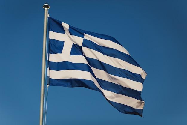 Grecka flaga z błękitnymi i białymi kolorami przeciw nieba tłu