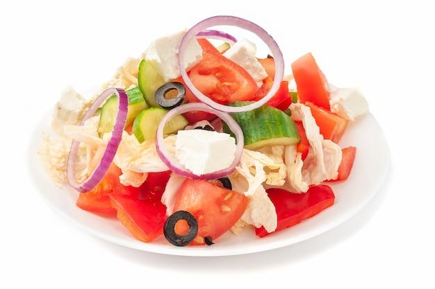 Grecka sałatka. z kapustą pekińską, pomidorem, ogórkiem, papryką, oliwkami, serem feta, cebulą i oliwą. na białym talerzu. odosobniony. na białym tle.