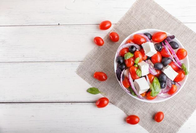 Grecka sałatka z świeżymi pomidorami cherry, serem feta, czarnymi oliwkami, bazylią i cebulą na białej drewnianej powierzchni.
