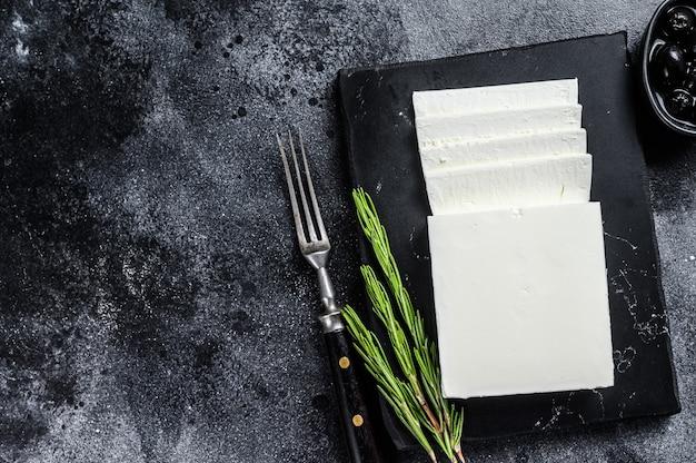 Grecka serowa feta z rozmarynem i oliwkami. czarny stół. widok z góry. skopiuj miejsce.