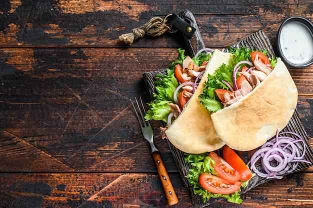 Grecki gyros zawinięty w chlebki pita z warzywami i sosem. ciemne drewniane tło. widok z góry. skopiuj miejsce.