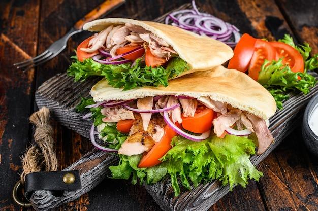 Grecki gyros zawinięty w chlebki pita z warzywami i sosem. ciemne drewniane tło. widok z góry.