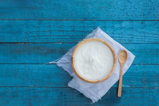 Grecki jogurt lub kwaśna śmietana w drewnianej misce na niebieskim stole widok z góry. zdrowe odżywianie.