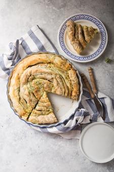 Grecki pasztetowy spanakopita nad betonowym tłem. pomysły i przepisy na wegetariańskie lub wegańskie ciasto szpinakowe z ciasta filo pokrojonego w plastry