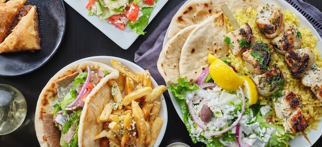 Grecki posiłek z kurczakiem souvlaki, gryosem, frytkami, sałatką i bakławą