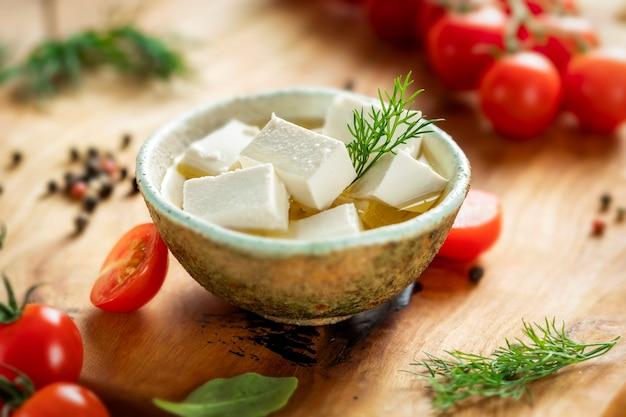 Grecki ser feta z oliwą i oliwkami, koperkiem i pomidorkami koktajlowymi na desce do krojenia