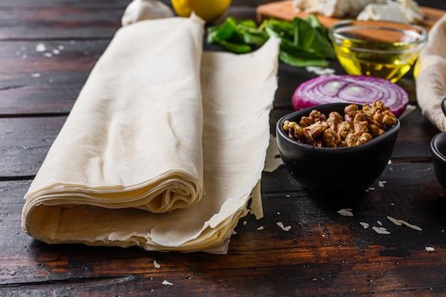 Grecki spanakopita składniki filo szpinak jaja feta widok z boku na ciemnym tle drewnianych