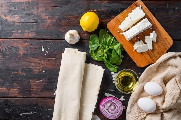 Grecki spanakopita składniki filo szpinak jaja feta widok z góry na ciemne drewniane tło dla tekstu.