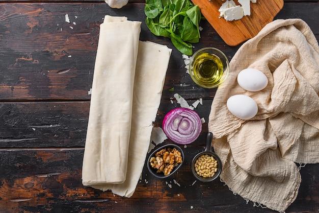Grecki spanakopita składniki filo szpinak jajka feta widok z góry na ciemne tło drewniane miejsca na tekst.