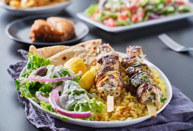 Grecki talerz souvlaki z kurczakiem, chlebkiem pita, surówką i ryżem
