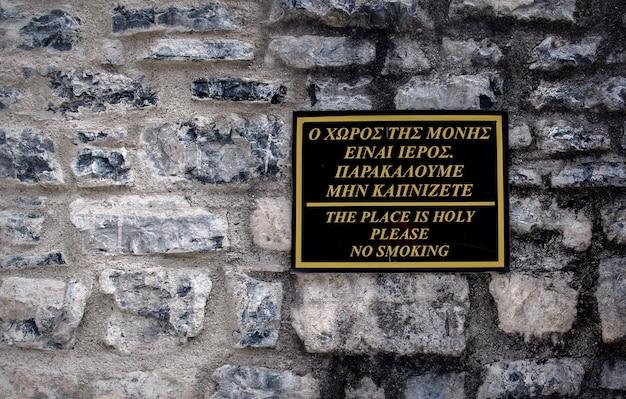 Grecki znak zakaz palenia na ścianie