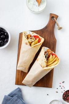 Greckie danie gyros z kurczakiem, frytkami, pomidorami, cebulą i pitą. kuchnia grecka.