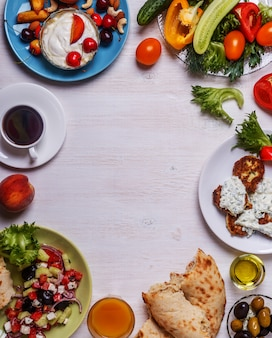 Greckie przekąski - placki z cukinii z sosem tzatziki, sałatka grecka, jogurt ze świeżymi owocami i orzechami, oliwki, warzywa i zioła