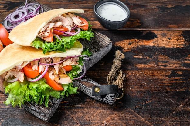 Greckie żyroskopy zawijane w pieczywo pita z warzywami i sosem na drewnianym stole. widok z góry.