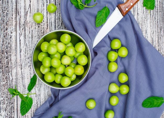 Greengages z liśćmi z nożem w metalowym rondlu na szarym drewnie i tkaninie piknikowej, widok z wysokiego kąta.