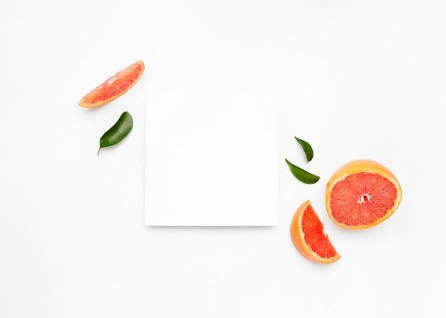 Grejpfrut i plasterki z liśćmi na białym tle na białej powierzchni