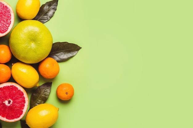 Grejpfruty i cytryny z liśćmi na zielonym tle. koncepcja bogatych zbiorów.