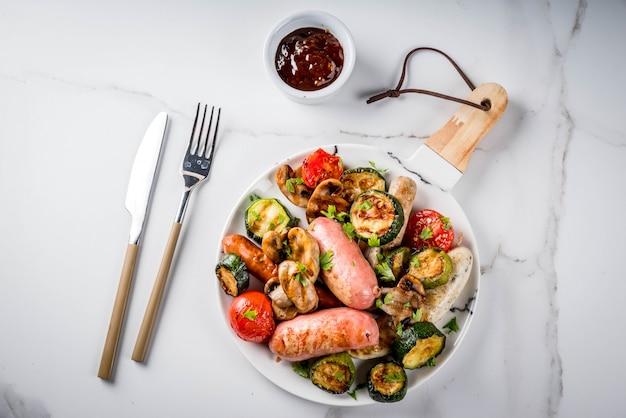 Grill. asortyment różnych grillowanych mięsnych kiełbas, z warzywami bbq - pieczarki, pomidory, cukinia, cebula. na białym marmurowym stole, na talerzu, z sosem. skopiuj widok z góry