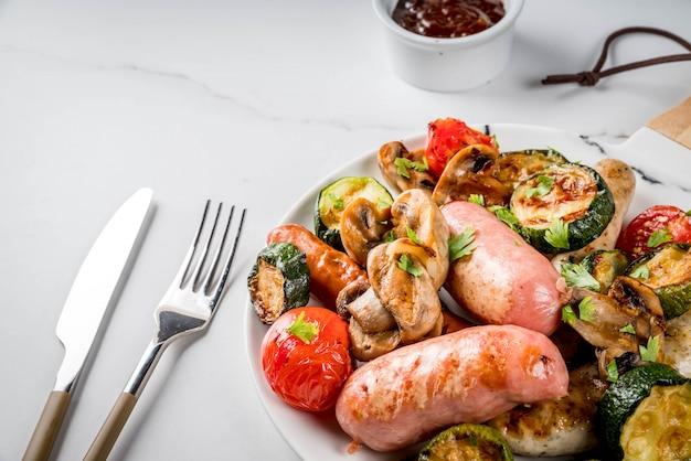 Grill. asortyment różnych grillowanych mięsnych kiełbas, z warzywami bbq - pieczarki, pomidory, cukinia, cebula. na białym marmurowym stole, na talerzu, z sosem.